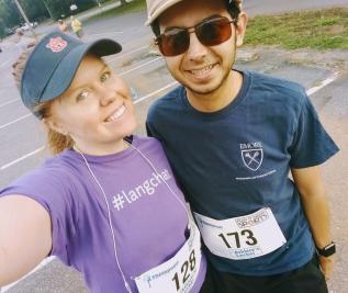 a redheaded woman in an Auburn visor and purple #langchat tee with a handsome man in an Emory shirt